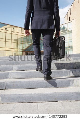 Close-up of confident businessman with briefcase walking upstairs - stock photo