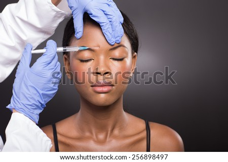 close up of cosmetic doctor injecting african woman forehead - stock photo