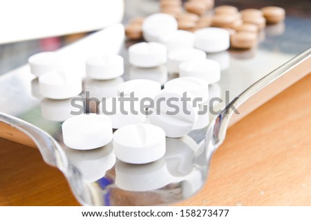 Close up of Counting tablets medical pills on stainless steel tray.(Health care and medical concept) - stock photo