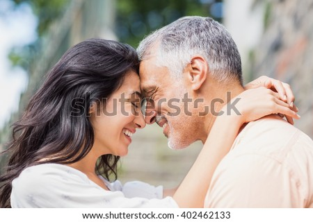 Close-up of couple embracing outdoors - stock photo