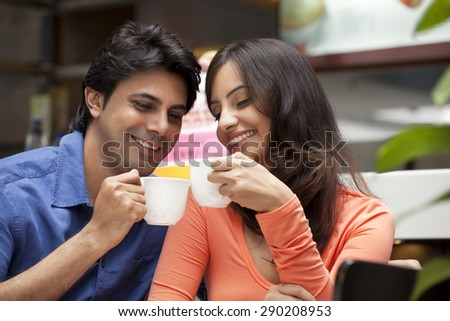 Close-up of couple enjoying their tea together in shopping mall - stock photo