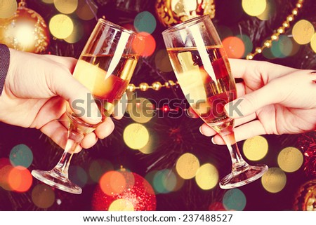 Close up of couple hands holding glasses of champagne over Christmas tree with lights  - stock photo