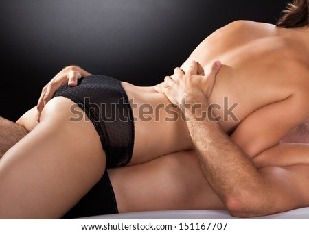 Close-up of couple having sex isolated on colored background - stock photo