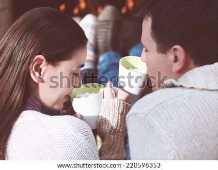 Close-up of couple holding cups with hot chocolate with marshmallows in front of lit fireplace - stock photo