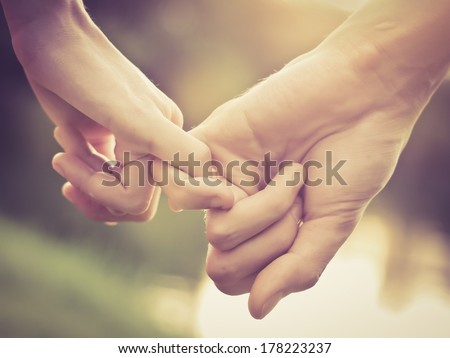 Close up of couple holding hands, vintage color - stock photo
