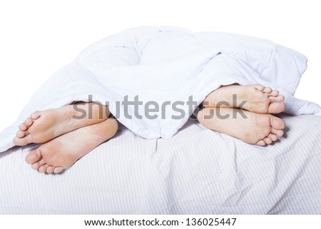 Close-up of couple's feet who had a fight on bed - stock photo