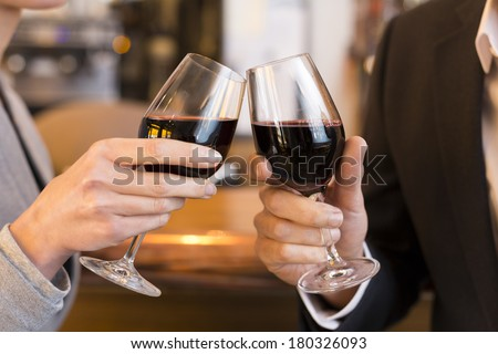Close Up of Couple Toasting with red wine glass in restaurant - stock photo