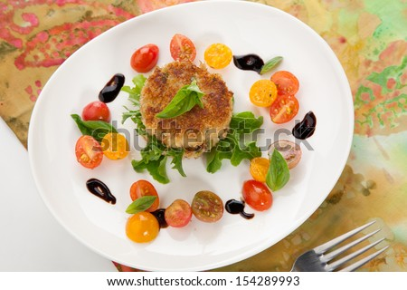 Close up of crab cakes and cherry tomato salad appetizer garnished with basil, and balsamic vinegar sauce.  - stock photo