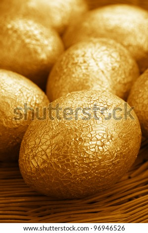 Close-up of crackle golden Easter eggs in wicker basket. - stock photo