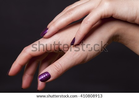 Close up of crossed over female hands decorated with purple fingernail paint over black - stock photo