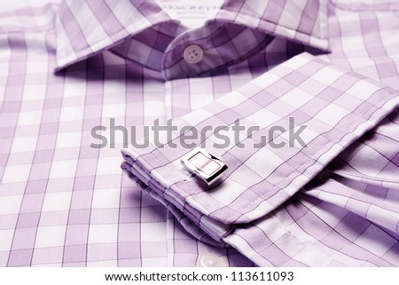 Close-up of cuff link on men's checkered shirt - stock photo