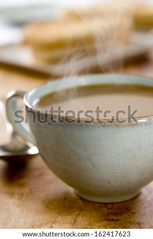 Close up of cup of steaming hot milk coffee at the breakfast table. - stock photo