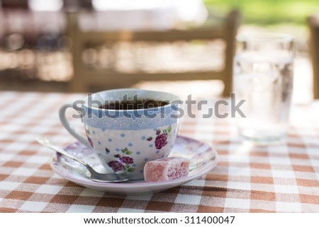 Close up of cup of traditional black coffee and Turkish delight  - stock photo