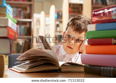 Close-up of cute boy reading book while preparing for lesson in library - stock photo