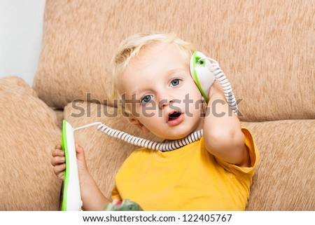 Close up of cute child boy on the phone. - stock photo