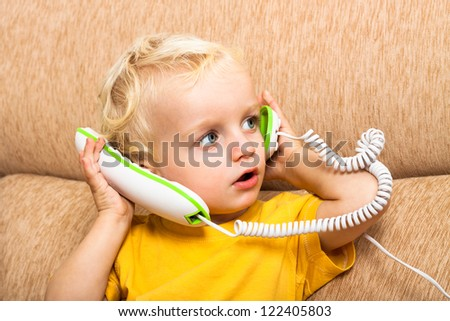 Close up of cute child boy playing with telephone. - stock photo
