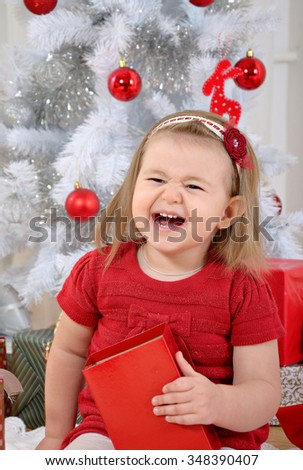 close-up of cute laughing little girl holding gift box with christmas tree on background - stock photo