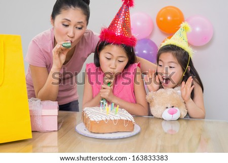 Close-up of cute little girls and mother blowing noisemakers at a birthday party - stock photo