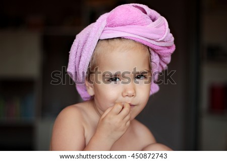Close-up of cute small girl with pink bath towel on her head biting her nails and looking slyly and archly, beauty and health concept, indoor portrait - stock photo