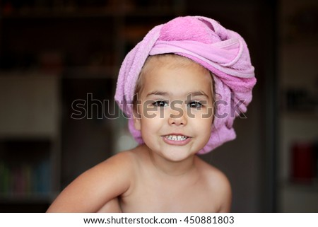 Close-up of cute small girl with pink bath towel on her head looking happily and showing her white teeth, beauty and health concept, indoor portrait - stock photo