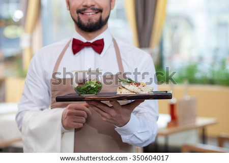 Close up of cute young waiter holding a tray of food. He is standing and smiling in the restaurant  - stock photo