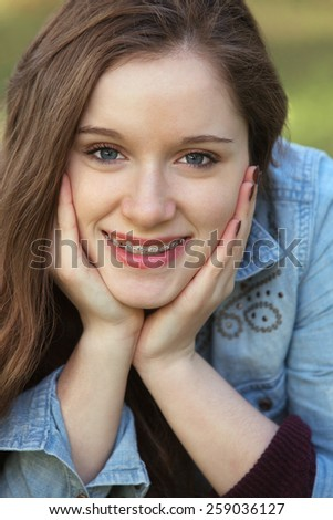 Close up of cute young woman with hands on cheeks - stock photo