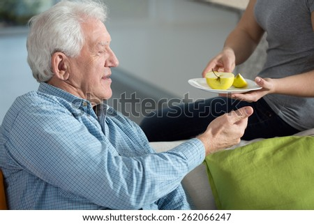 Close-up of daughter caring about senior father - stock photo