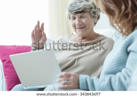 Close-up of daughter teaching elder mum using laptop - stock photo