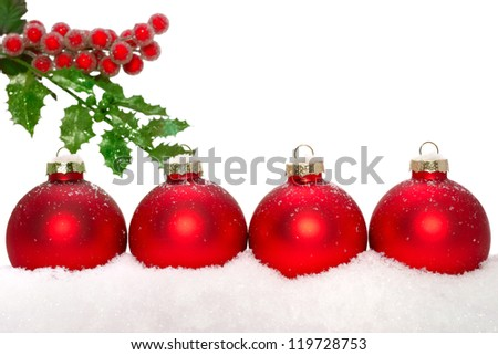 Close up of decorative Christmas ornaments on the snow, and holly. - stock photo