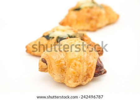 Close up of delicious and fresh baked croissants with vegetable and cheese toppings for tea time - stock photo