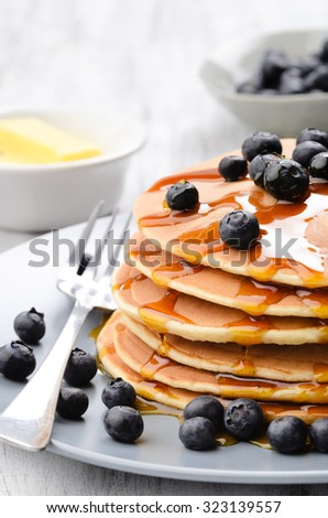Close up of delicious pancake stack with blueberries and flowing dripping maple syrup - stock photo
