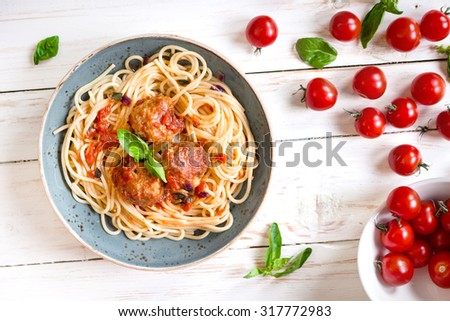 Close-up of delicious spaghetti with meatballs and tomato sauce on a plate. Serving on a white rustic wooden table. An Italian-American dish. Top view. Selective focus - stock photo