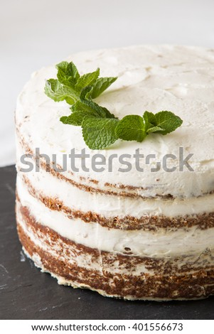 Close-up of delicious white cream icing cake with mint leaves served on the black board. Homemade naked cake with cream, decorated with mint. Birthday pie. - stock photo