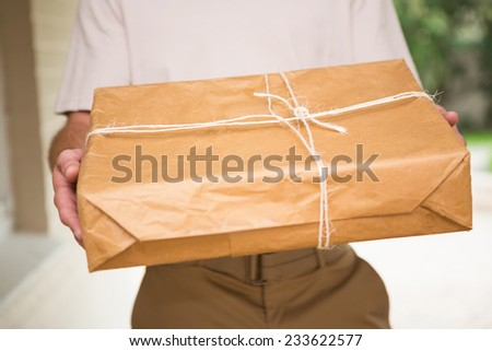 Close up of delivery man giving package outside the warehouse - stock photo