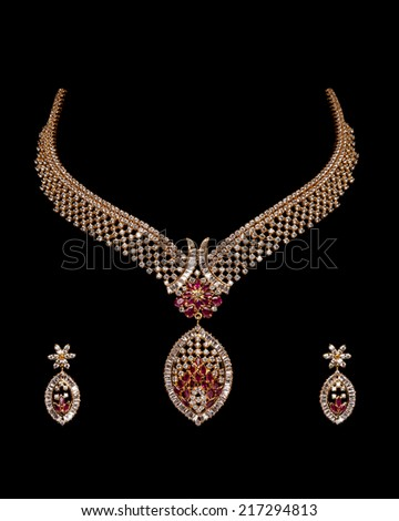 Close up of diamond and gold necklace with earring  on black background - stock photo