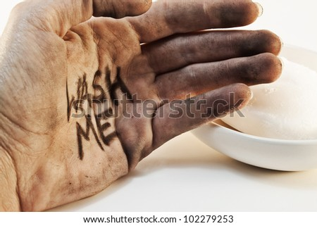 Close up of dirty caucasian bare hand with wash me written on palm and soap in background isolated on white background. - stock photo