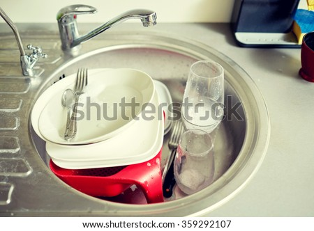 close up of dirty dishes washing in kitchen sink - stock photo