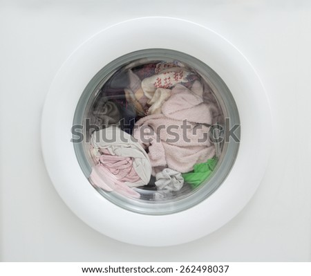 close up of dirty laundry inside of washing machine - stock photo