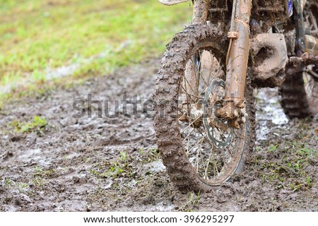 Close-up of dirty wheel of motocross bike in mud. Bokeh. - stock photo