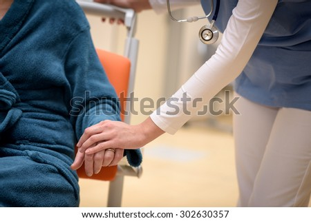 Close-up of doctor holding senior patient hand sitting in wheelchair - stock photo