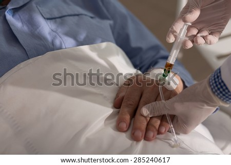 Close-up of doctor injecting the medicine to his older patient - stock photo