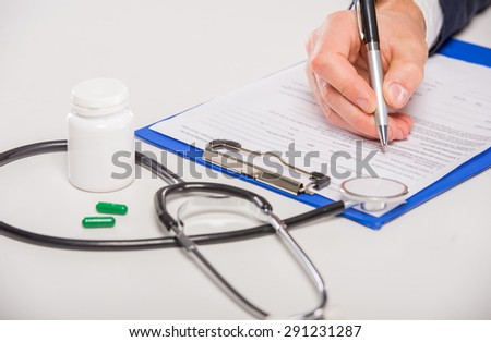 Close-up of doctor's hand writing down a recipe. - stock photo