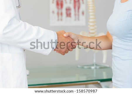 Close up of doctor shaking hands with patient in bright office - stock photo