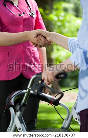 Close-up of doctor shaking hands with patient outdoors - stock photo