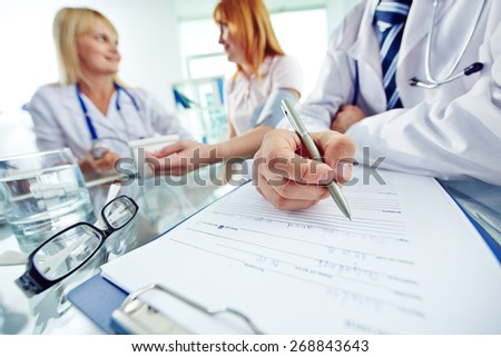 Close-up of doctor with pen filling in personal data - stock photo