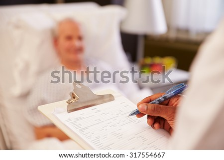 Close Up Of Doctor Writing On Senior Male Patient's Chart - stock photo