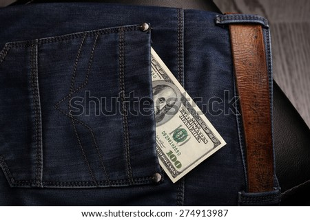close-up of dollar bills pocket denim trousers, studio  - stock photo