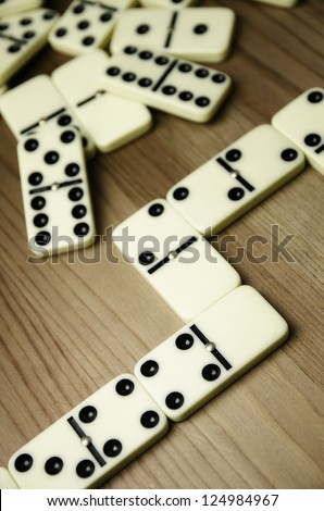 Close up of domino with black dots on wooden background - stock photo