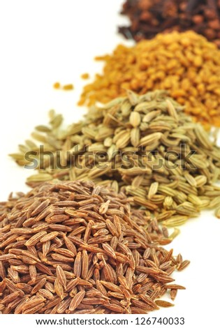 close up of dried seeds of spices piled on white - stock photo