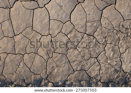 Close up of dry cracked soil on filed - stock photo
